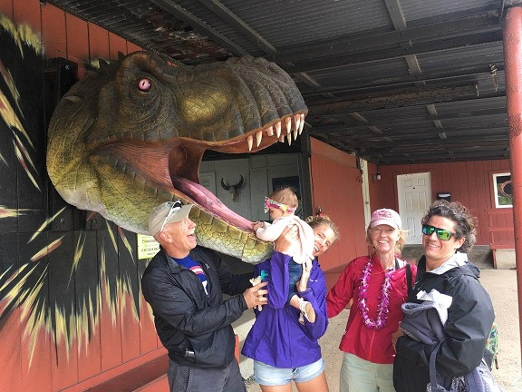 All of us standing around and LeiLei climbing into a full size dinosaur mouth.